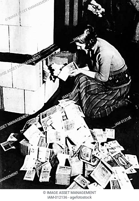 Hyperinflation in Germany post World War I: Woman uses bank notes to fuel a stove