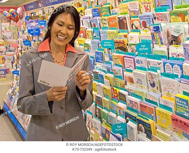 Woman reading greeting card in store