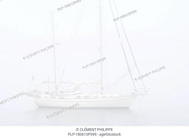 Sailboat / sailing boat / yacht with lowered sails anchored at sea during bad visibility due to thick fog / dense mist