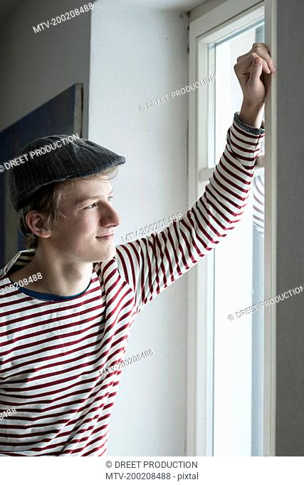 Young man smiling and looking through the window, Bavaria, Germany