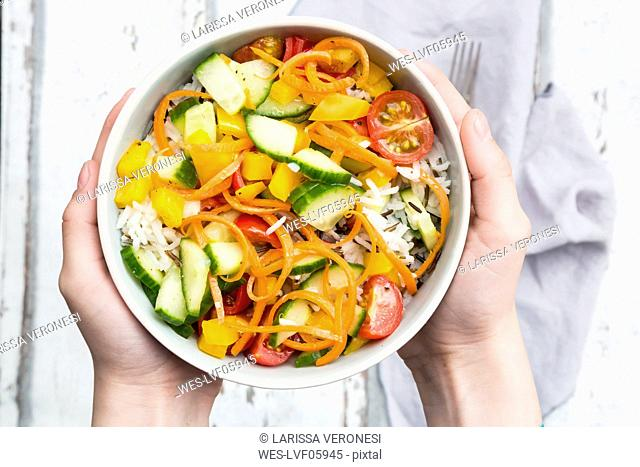Hands holding bowl of rice salad with mixed vegetables