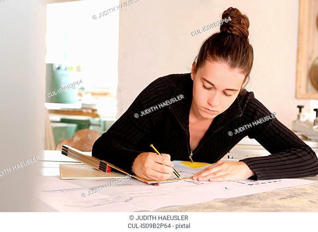 Woman drawing blueprint