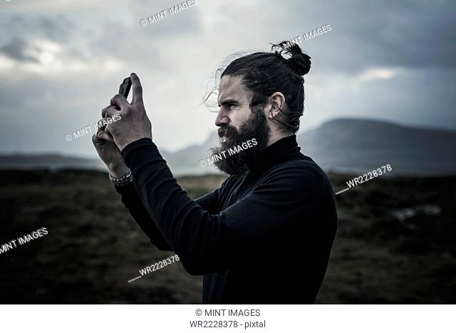 A man taking a photograph with a smart phone