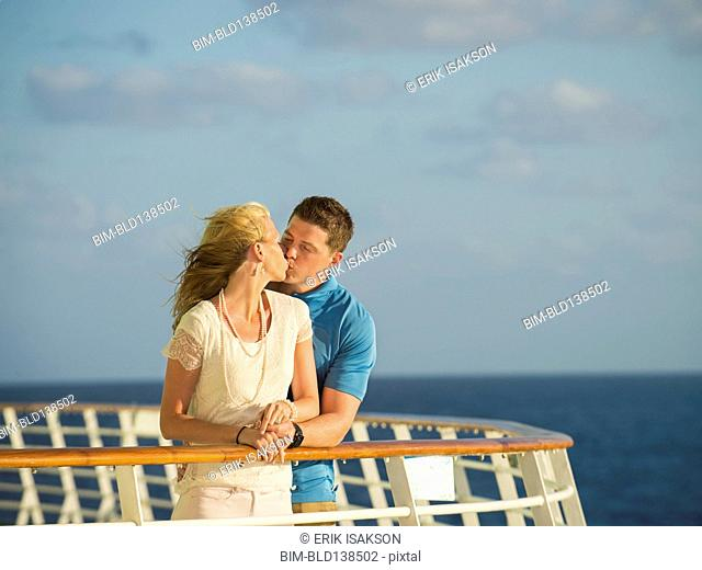Caucasian couple kissing on boat deck