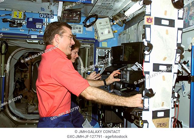 A crew member used a digital still camera to take a picture of members of the Expedition Two crew at work in the Destiny laboratory