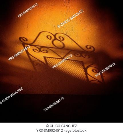 The shadow of a chair is cast on an orange wall in Flycatcher Inn hotel in Santa Elena, Yucatan, Mexico
