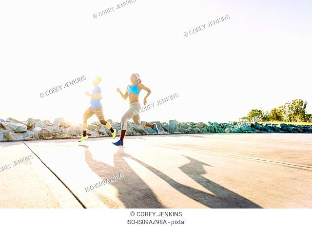 Man and young woman training, running on sunlit coast, downtown San Diego, California, USA