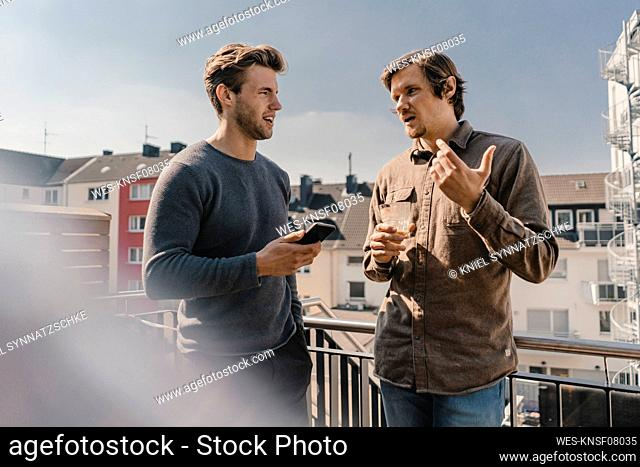 Colleagues having a break on the balcony, talking, using smartphone