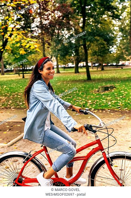 Smiling young woman riding a bike in a park