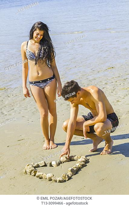 Young couple on beach forming symbolic heart from group of stones