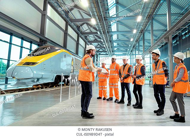 Teacher talking to apprentices at railway engineering facility