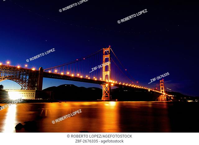 The amazing Golden Gate Bridge seen on a long exposure at night, with the lights reflected on the water and a plane moving in the sky, San Francisco, California