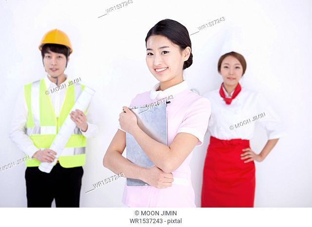 three persons posing dressed as different professions