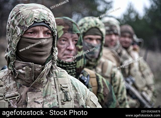 Army elite forces tactical group soldiers, skilled commandos squad, members wearing camouflage uniform, hiding faces behind masks