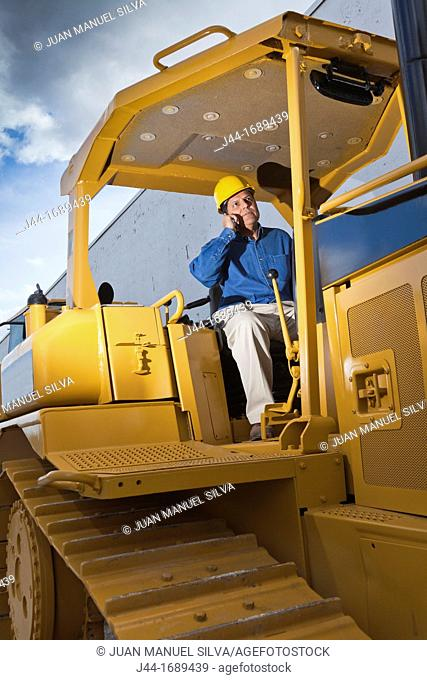 Man with hard hat on bulldozer using mobile phone