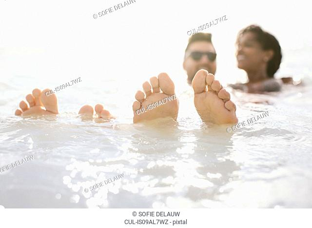 Couple with feet up in sea, Tuscany, Italy