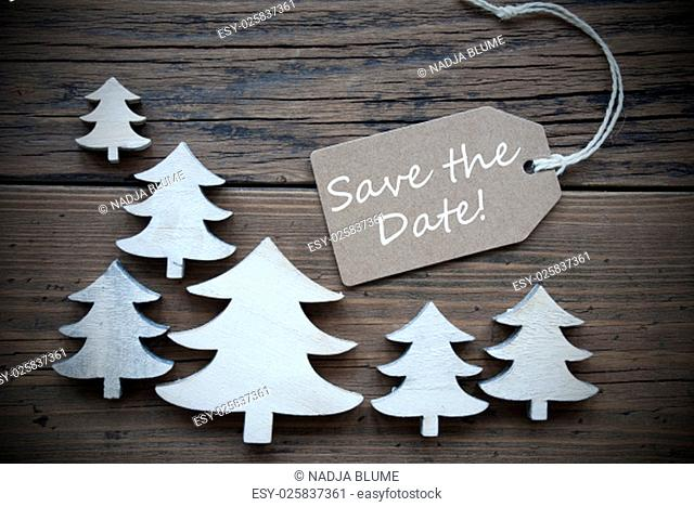 Brown Christmas Label With Ribbon On Wooden Background With White Christmas Trees. Vintage Style. Label With English Text Save The Date For Christmas Or Season...