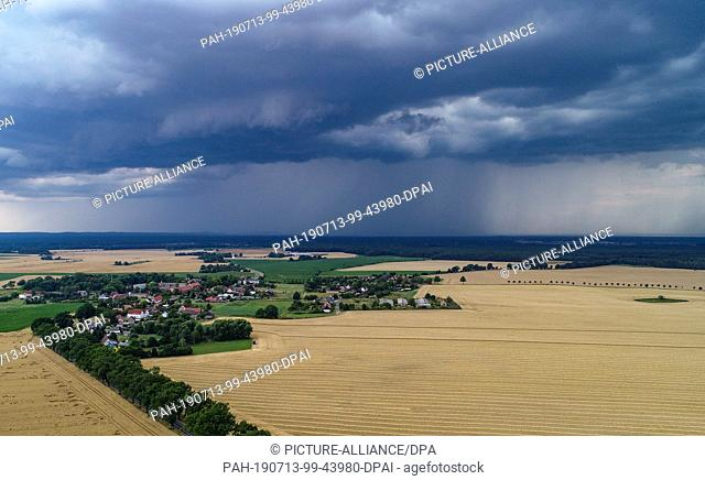 13 July 2019, Brandenburg, Petersdorf: Thunderstorm clouds are moving over the landscape in the district Oder-Spree (aerial photo with a drone)