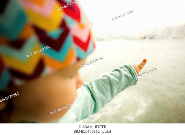 Caucasian baby girl pointing at ocean from window
