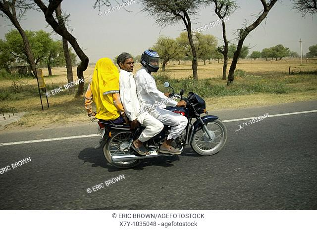 Three riders on a motorcycle on a highway in India