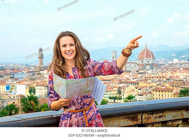 Smiling young woman with map pointing against panoramic view of florence, italy