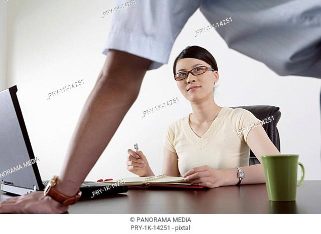 Businesswoman looking at businessman in an office
