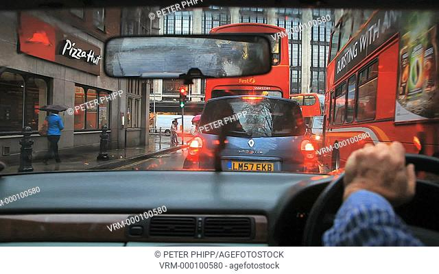 Driving in Kensington on a rainy wet day with busy traffic in London