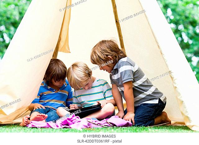 Boys using tablet computer in tent