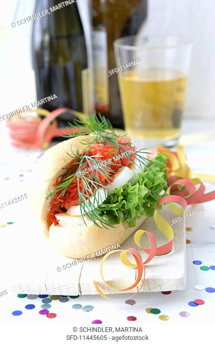 A salmon roll with egg, lettuce and dill, decorated with paper streamers and confetti
