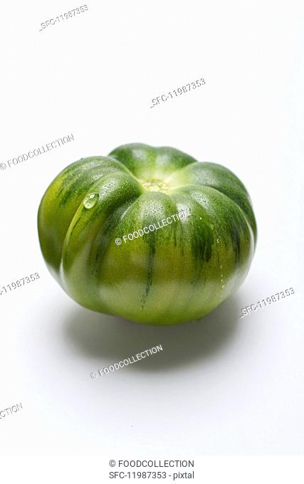 A green tomato on a white surface