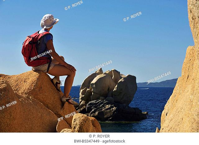female wanderer sitting on a rock and admiring the view on a bizarre rock formation, France, Corsica
