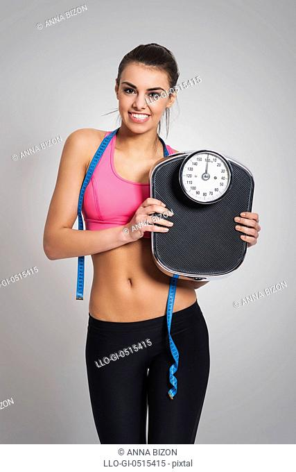 Satisfied fit woman with weight scale. Debica, Poland