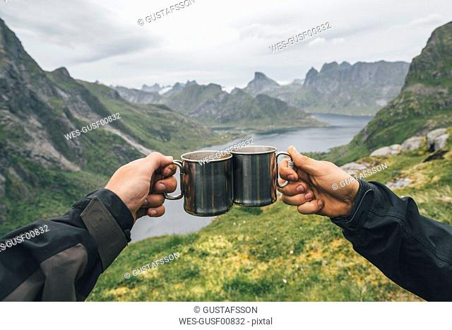 Norway, Lofoten, Moskenesoy, Two people toasting with tin cups
