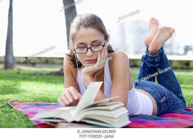 Girl lying down reading in park