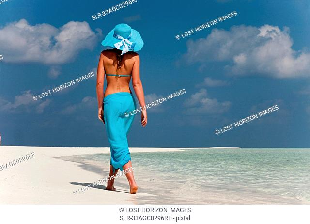 Woman walking on tropical beach