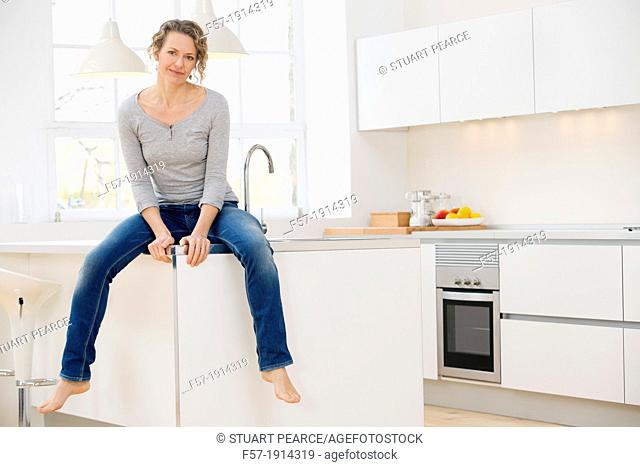 Independent young woman sitting her kitchen