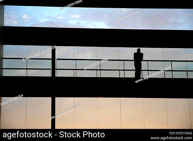 worker inside the building silhouette at sunset