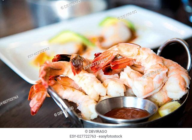 A serving of boiled shrimp with cocktail sauce