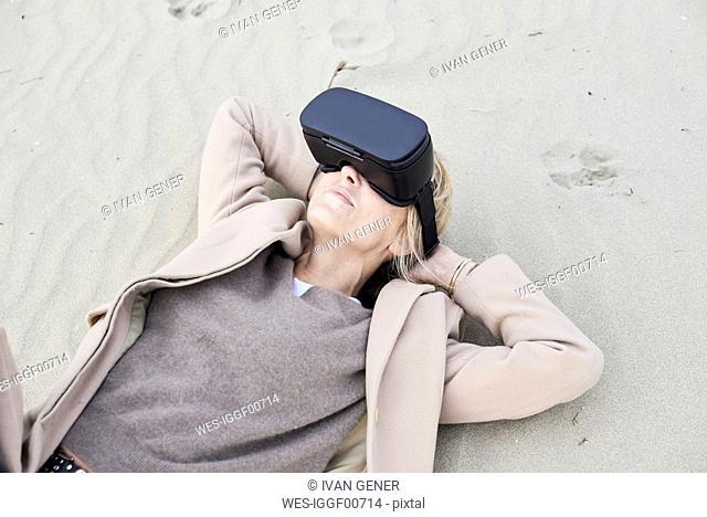 Spain, Menorca, senior woman lying on the beach in winter using VR glasses