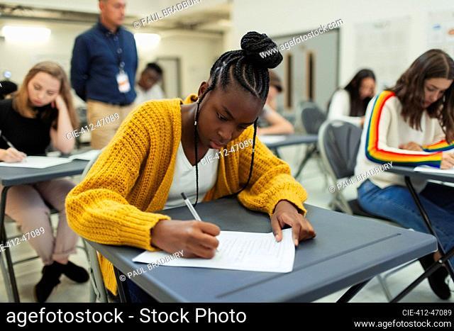 Focused high school girl student taking exam at desk