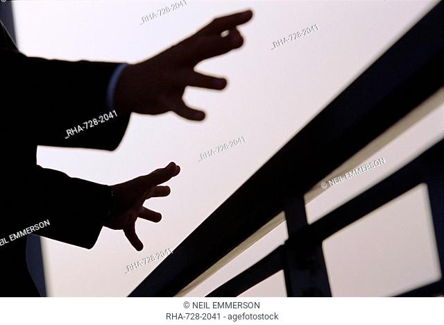 A man's outstretched hands about to grasp railings