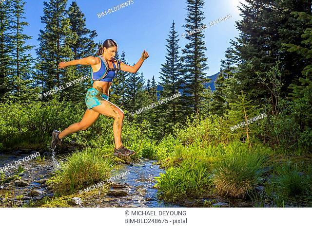 Hispanic woman jumping over stream