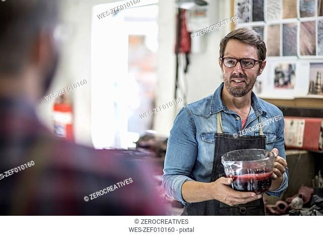 Artist holding mould wax in a jar looking at colleague