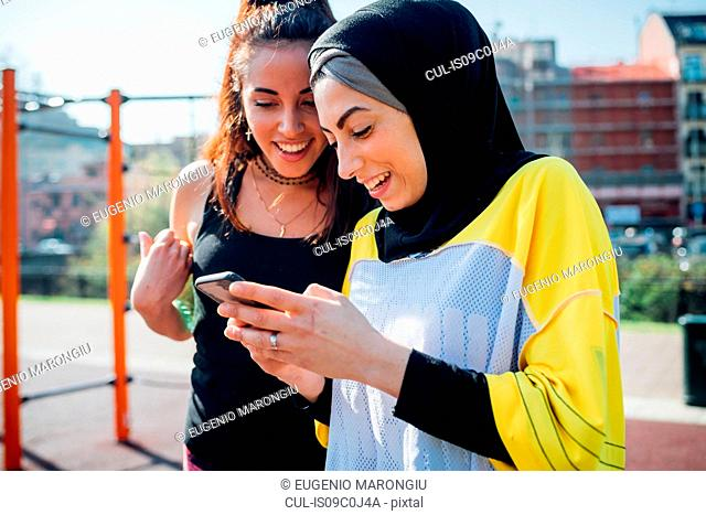 Calisthenics class at outdoor gym, two young women looking at smartphone