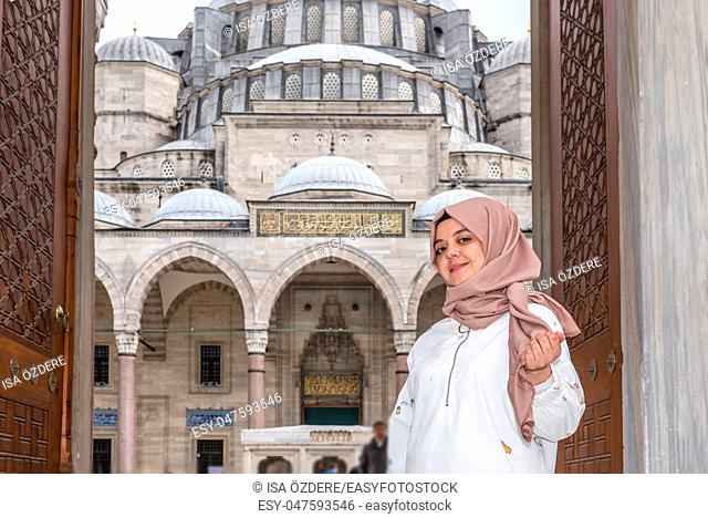Beautiful Muslim woman in headscarf and fashionable modern trendy clothes poses at gate of Suleymaniye Mosque in Istanbul, Turkey