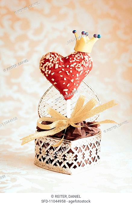 A heart-shaped cake pop decorated with a crown