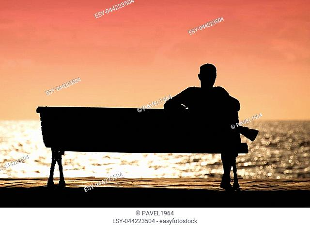Silhouette of men sitting alone on the bench in front of the sea