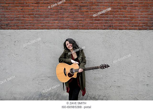 Portrait of young woman with acoustic guitar leaning against wall