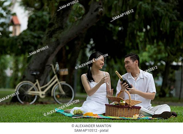 Singapore, Couple on picnic blanket with bottle of wine