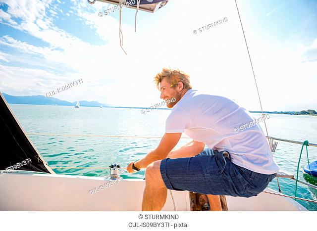 Young man sailing on Chiemsee lake, Bavaria, Germany